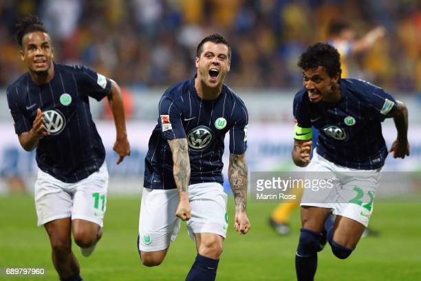 Vieirinha of Wolfsburg celebrates his team's first goal with team mates Daniel Didavi and Luiz Gustavo during the Bundesliga Playoff leg 2 match...