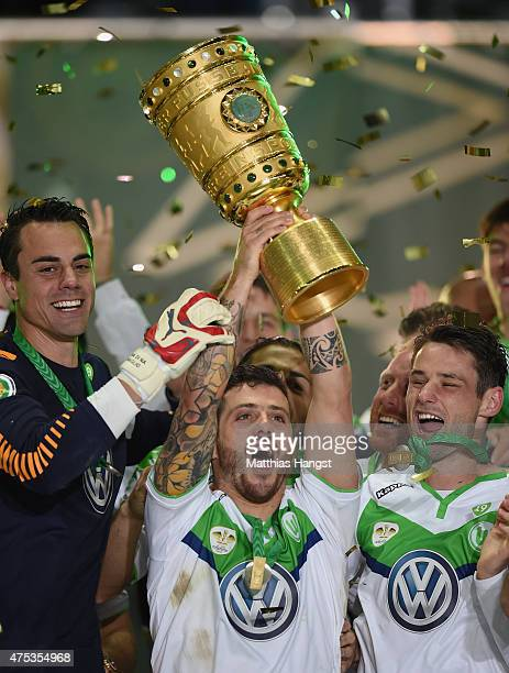 Vieirinha of Wolfsburg lifts the trophy to celebrate after winning the DFB Cup Final match between Borussia Dortmund and VfL Wolfsburg at...