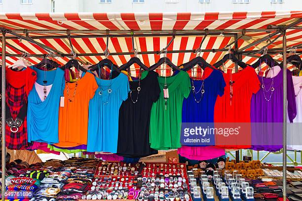 Viele bunte Shirts zum Verkauf auf einem Markt Konkurrenz für Textilhandel