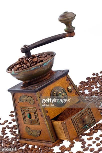 Viele Kaffeebohnen liegen neben einer Kaffeemühle Frisch gemahlener Kaffee