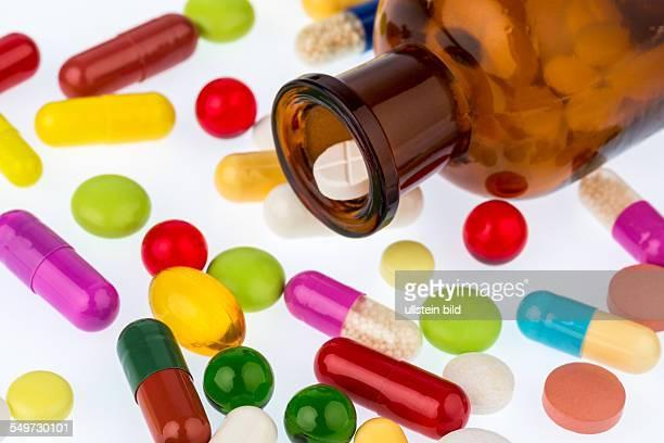 Viele Tabletten mit einem Glasbeghäter Symbolfoto für Sucht und Kosten in der Medizin und bei Medikamenten