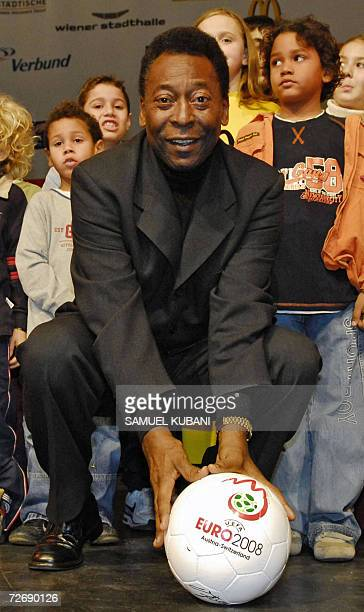 Brazilian football legend Edson Arantes do Nacimento known as Pele poses surrounded by children with the EURO 2008 ball 01 December 2006 during his...