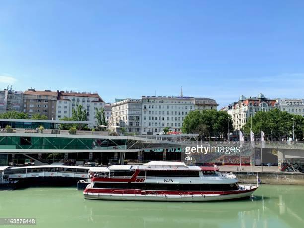 wien, österreich: schiffe auf der donau und gebäude im hintergrund - advertising column stock-fotos und bilder