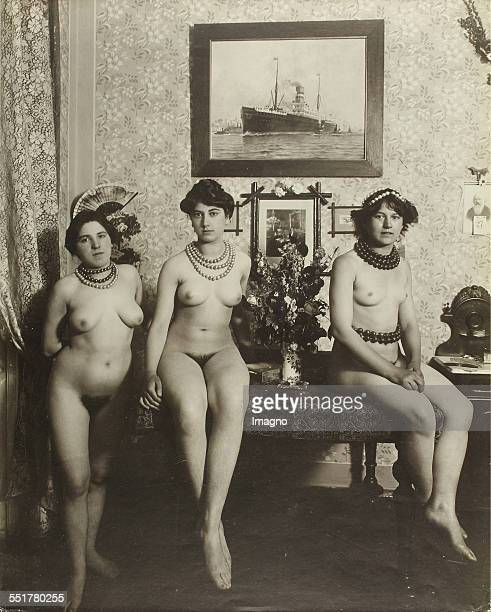 Vienna 'Nackedeien' of the Gründerzeit Three naked girls decorated with head and neck chains on and around a table in the living room 1906 Photograph