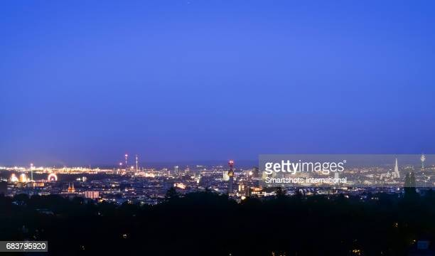 Vienna skyline illuminated at dusk with Cathedral spire and financial district, Austria