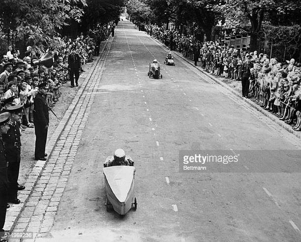 Vienna small fry in a streamlined home made racer, streaks up to the finish line to win his heat in the Vienna Soap Box Derby of 1952. The event was...