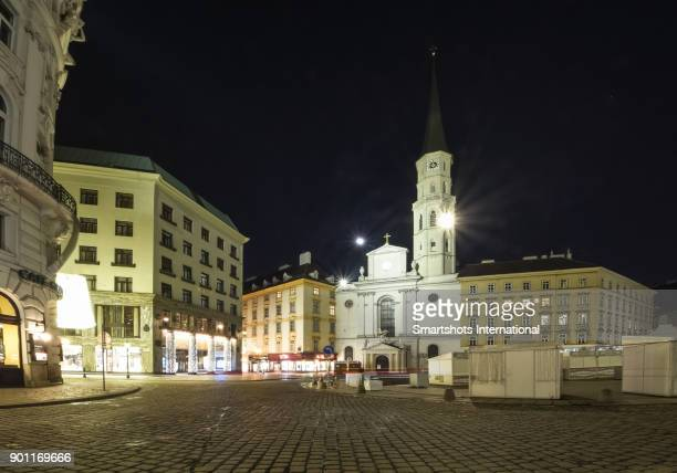 Vienna's Michaelerplatz illuminated at night with no people and with facade of church of St Michael centered, Vienna, Austria