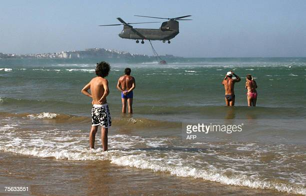 Firefighting helicopter resupplies himselves with seawater as tourists go swimmimg on the beach of Vieste, 25 July 2007, a day after wildfires...