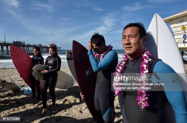 Viet Bui joins hundreds of people as they gather on the sand during the start of a paddle out to honor Pierre Agnes CEO of Quiksilver in Huntington...