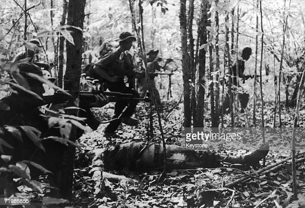 A Viet Cong detachment going into battle during the Vietnam War January 1967 In the foreground is the body of a dead American soldier