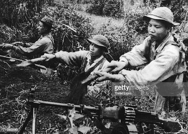 Viet Cong soldiers dig a trench to be used as a heavy machine gun position during the Vietnam war circa 1968