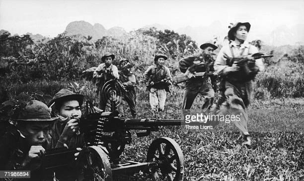 Viet Cong soldiers moving forward under covering fire from a heavy machine gun during the Vietnam War, circa 1968.