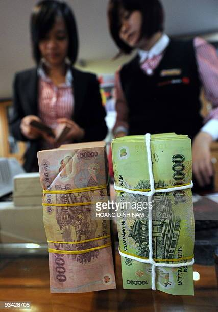 Vietamese commercial bank employee counts Vietnamese dong notes at a branch in Hanoi on November 26, 2009. Vietnam's central bank devalued its...