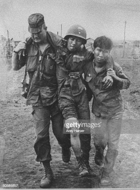 Vietnam adviser Army Gen Norman Schwarzkopf helping S Vietnamese soldier carry his wounded buddy to medical station after an attack