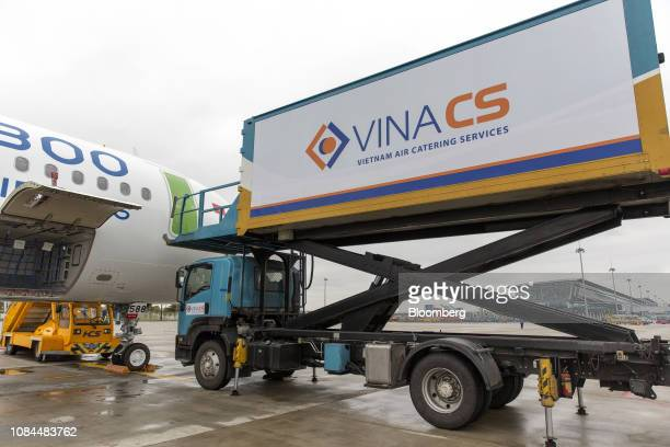 A Vietnam Air Catering Services JSC container stands next to an Airbus SE A321 Neo aircraft operated by FLC Group JSC's Bamboo Airways at Noi Bai...