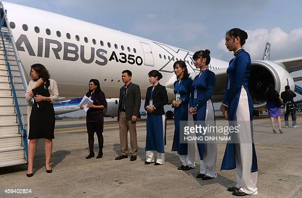 Vietnam Airlines ground staff in traditional dress 'ao dai' stand next to an Airbus A350XWB prior to a demo flight at Hanoi's Noi Bai airport on...