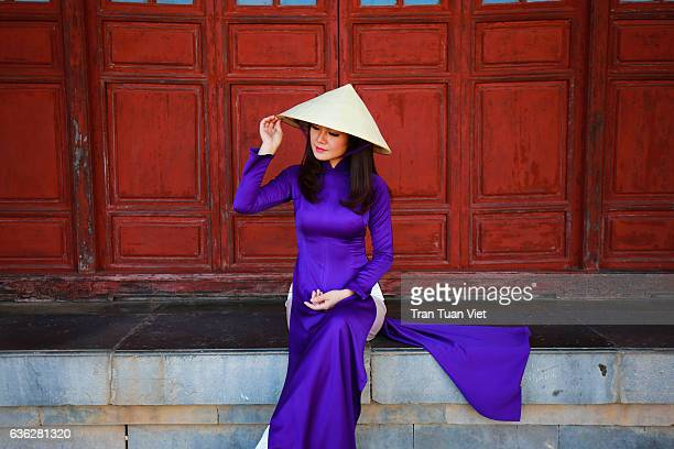 vietnam ao dai - vietnamese woman in ao dai traditional dress near red doors - long dress stock pictures, royalty-free photos & images