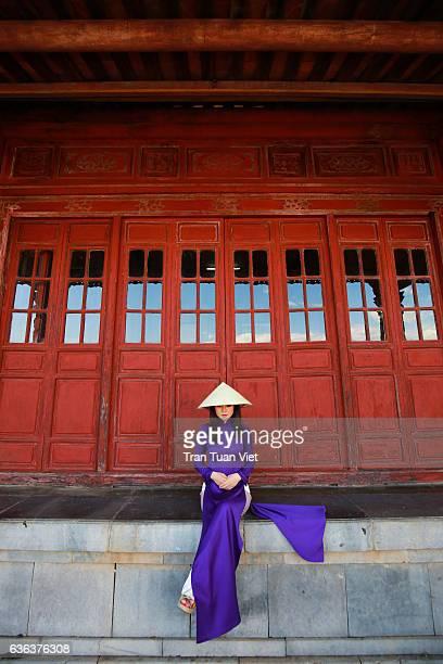 Vietnam Ao Dai - Vietnamese woman in Ao Dai traditional dress sitting near red doors