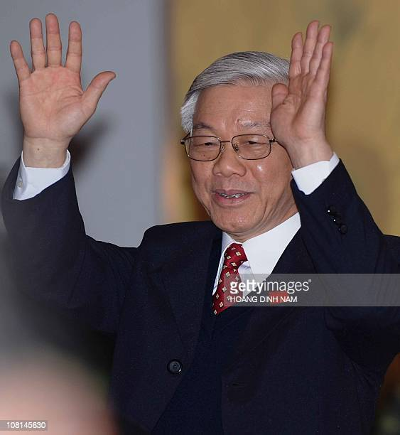 Vietnam Communist Party's newly elected Secretary General Nguyen Phu Trong salutes the media as he arrives at a press conference held at the end of...