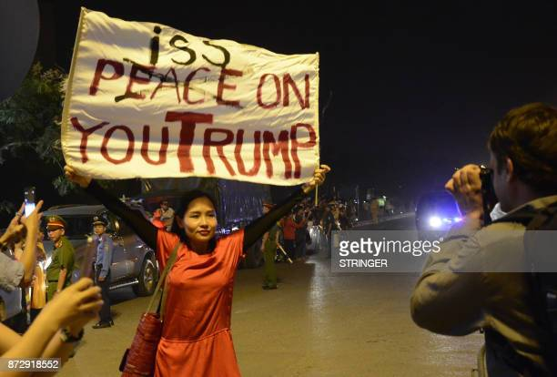 Vietnam dissident musician Mai Khoi also known as the 'Lady Gaga' of Vietnam holds up a banner reading 'Piss on you Trump' in Hanoi on November 11 as...
