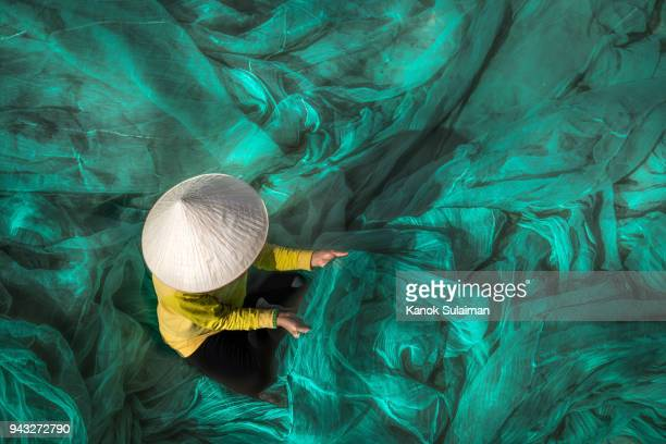 vietnam fishermen are repairing fishing nets - vietnam stock pictures, royalty-free photos & images