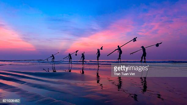 vietnam - fishermen going with stilts, hanging fishing tools on the beach, in sunrise at nam dinh province - ナムディン ストックフォトと画像
