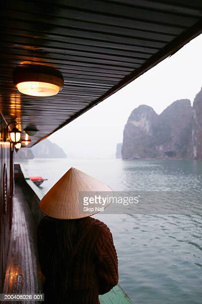 Vietnam, Halong Bay, person wearing straw hat on boat, rear view