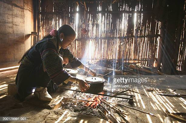 Vietnam, Han Thao Village, woman heating water pot