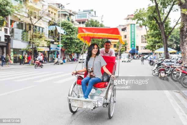 vietnam, hanoi, young woman on a riksha exploring the city - rickshaw stock photos and pictures
