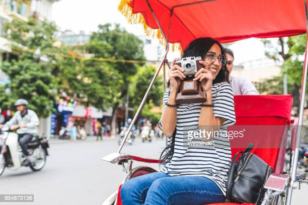 vietnam, hanoi, young woman with old-fashioned camera on a riksha - human powered vehicle stock photos and pictures
