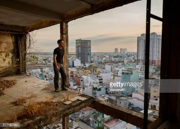 Vietnam, Ho Chi Minh City, man standing in ruin of a skyscraper