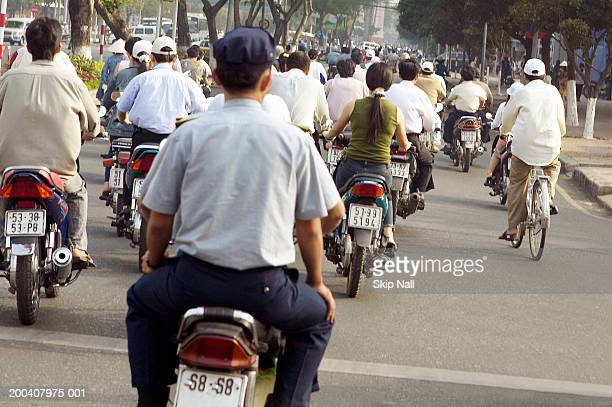 Vietnam, Ho Chi Minh City, people on scooters and bicycles, rear view