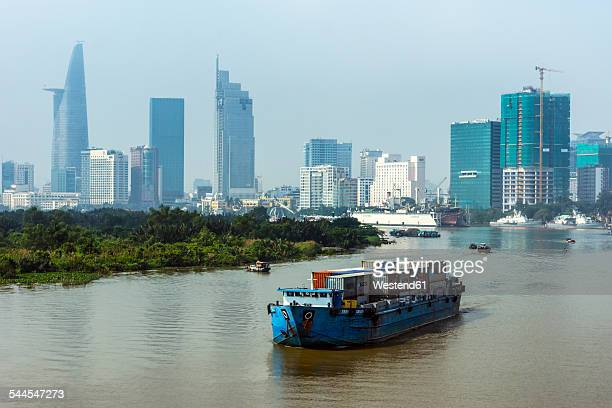 vietnam, ho chi minh city, ship on saigon river and skyscrapers with bitexco financial tower - saigon river stock pictures, royalty-free photos & images