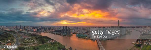vietnam - ho chi minh city sunset panorama at saigon river & thu thiem bridge aerial view. - thiem stock pictures, royalty-free photos & images