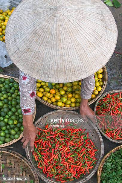 Vietnam, Hoi An, woman bending over vegetables at market