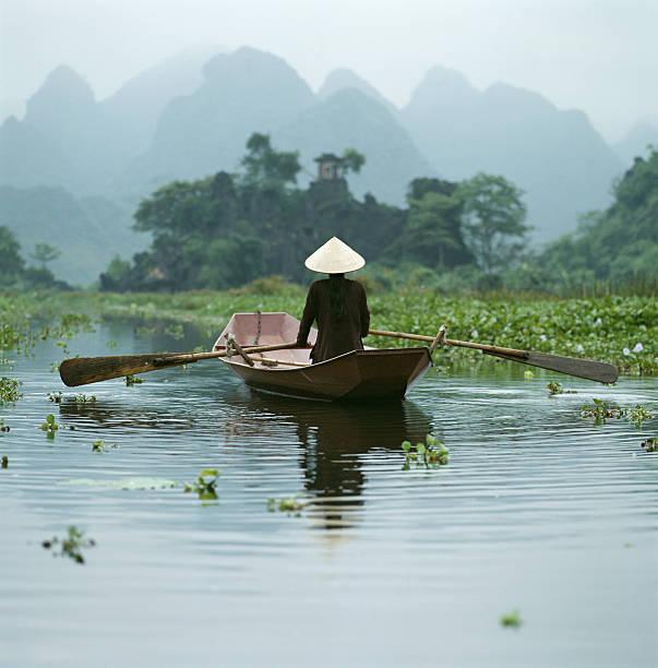 Vietnam, Near Hanoi, Perfume Pagoda, young woman  in boat , rear view