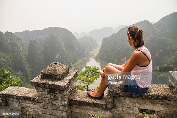 Vietnam, Ninh Binh, Young tourist looking down to Tom Coc valley