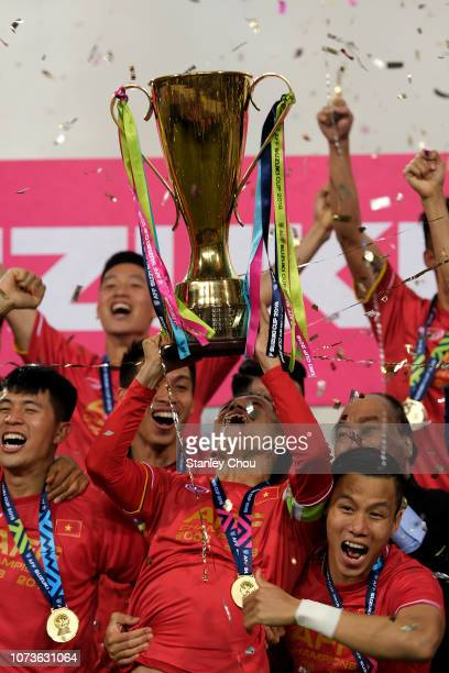 Vietnam players celebrate with the Suzuki Cup after they defeated Malaysia 1-0 during the AFF Suzuki Cup final second leg match between Vietnam and...