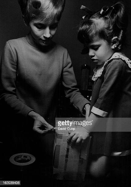 DEC 20 1969 DEC 22 1969 DEC 23 1969 Vietnam * US Troops * Pows A Present for Daddy Ray Suzanne Salzarulo holds package while her mother Mrs Ray...