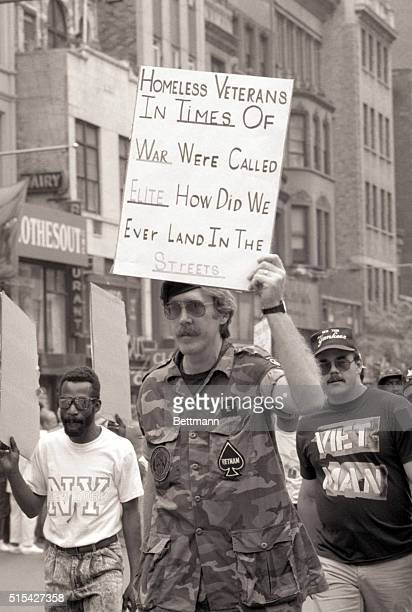 Vietnam veteran holding sign which says Homeless Veterans in Times of War Were Called Elite How Did We Ever Land in the Streets on Memorial Day in...
