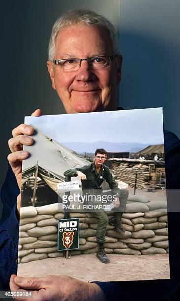 US Vietnam veteran Larry Kolp stands in his Arlington Virginia living room February 23 with a photo of him taken in taken in Duc Pho Vietnam in 1967...