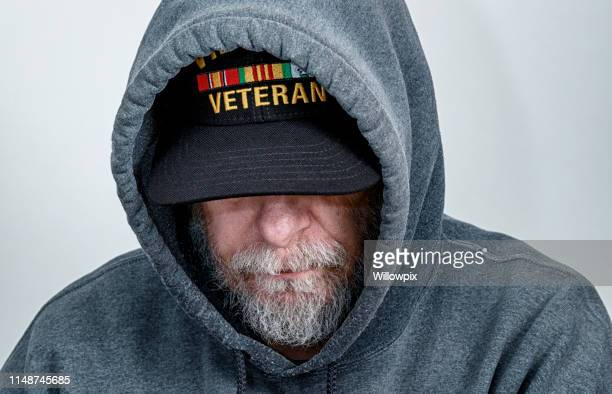vietnam war usa military veteran wearing hoody looking down - veteran stock pictures, royalty-free photos & images