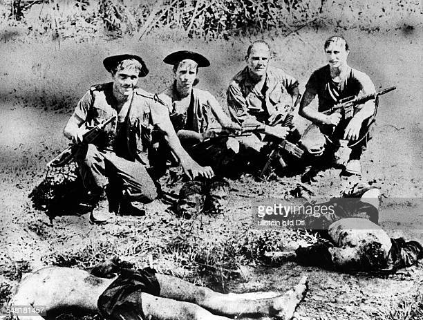 Vietnam War USsoldiers posing with the heads of two beheaded Vietcong August 1969