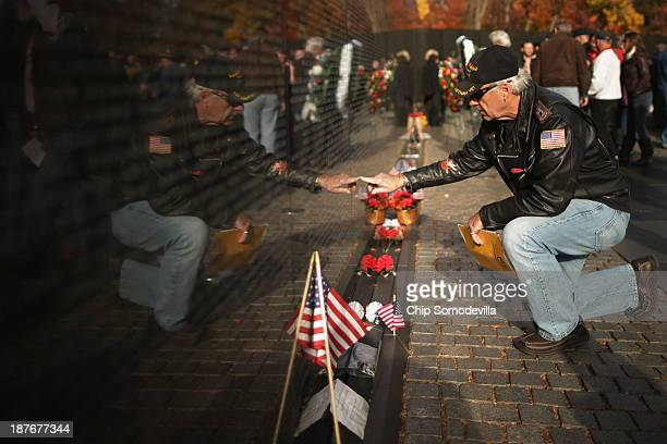 Vietnam War veteran Bruce Hackert of Southport, North Carolina touches the place on the Vietnam Veterans Memorial where a friend's name is etched on...