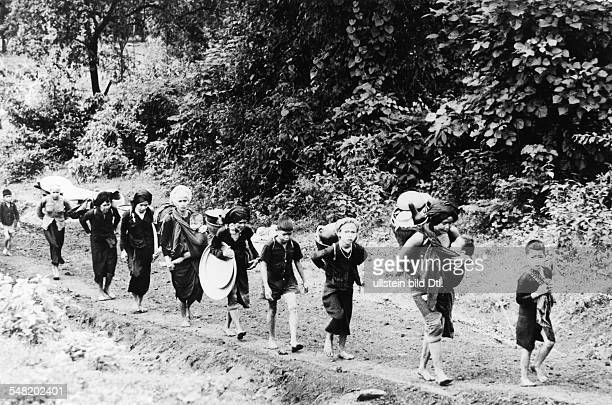 Vietnam War Women of a hill tribe coming back from a military training camp where their husbands had been conscripted South Vietnam 1962