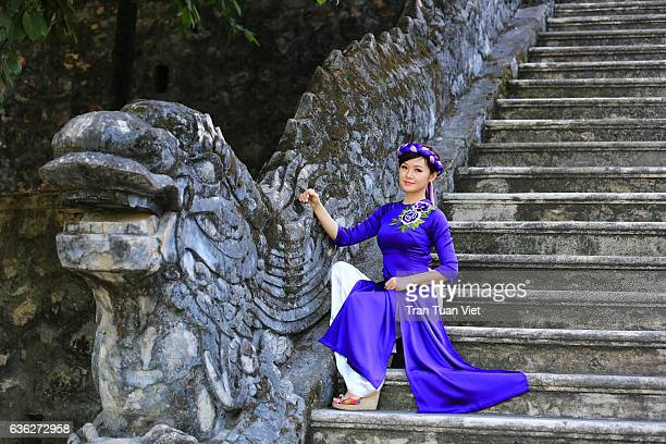 Vietnam - Woman in Ao Dai traditional dress sitting in Khai Dinh stomb