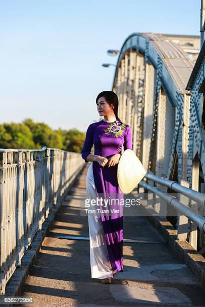 vietnam - woman in ao dai traditional dress walking in trang tien bridge, hue - long dress stock pictures, royalty-free photos & images
