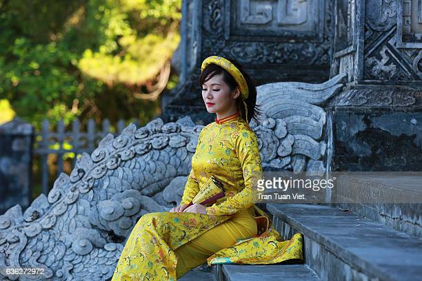 Vietnam - Woman in yellow Ao Dai traditional dress in Khai Dinh stomb