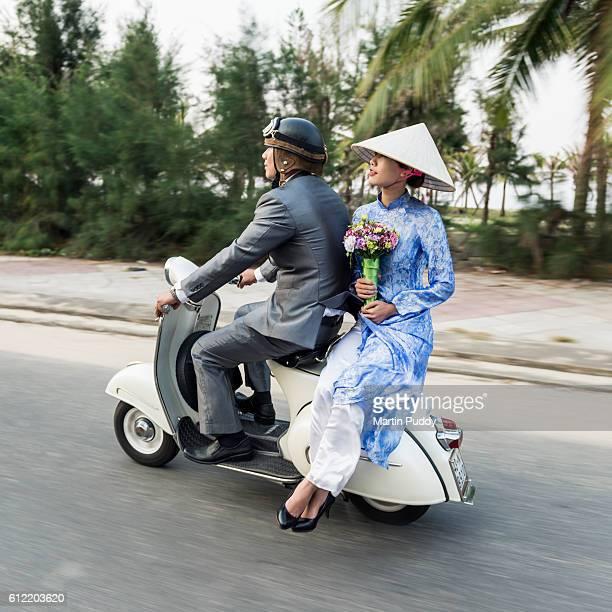 Vietnam, young couple riding along on classic Vespa