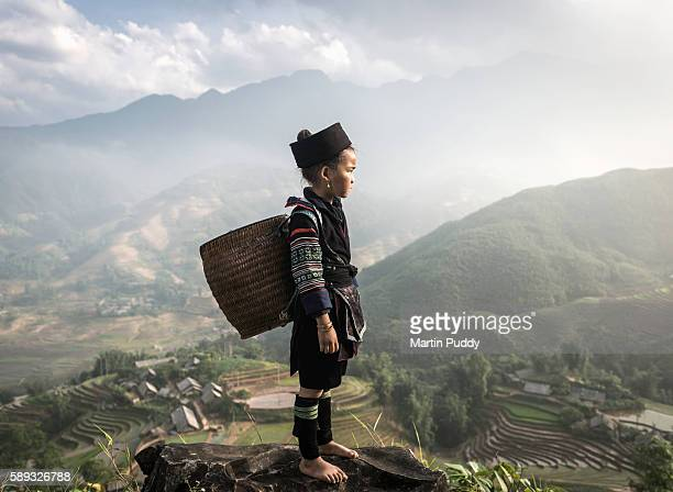 vietnam, young girl of black hmong hilltribe, wearing traditional clothing, standing on hillside, overlooking rice terraces - 発展途上国 ストックフォトと画像